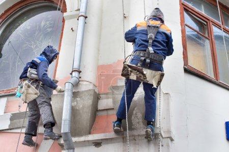 Foto de Dos trabajadores de la construcción colgados de una cuerda de un edificio alto - Imagen libre de derechos