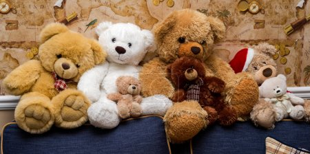 A group of cute teddy bears sitting together on the sofa