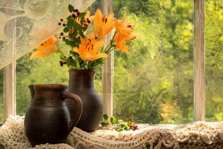Photo pour Asiatique Hybrides bouquet de lis orange sur un rebord de fenêtre par une journée pluvieuse ensoleillée. Émotions de bonne humeur de couleur orange . - image libre de droit