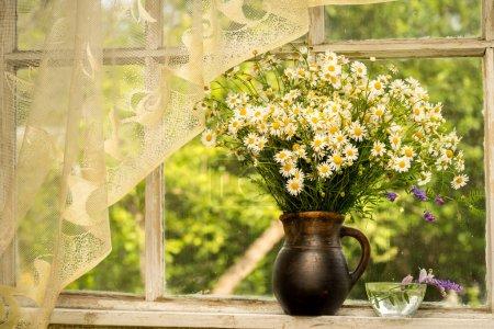 Photo pour Nature morte bouquet de camomille sur un rebord de fenêtre dans un jour de pluie ensoleillé - image libre de droit