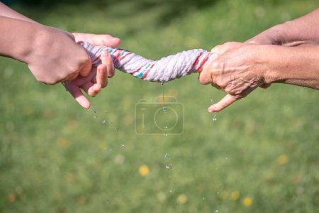 Photo pour Mains serrer le tissu humide sur un fond d'herbe - image libre de droit