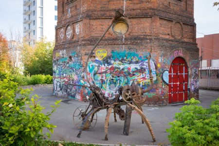 Izhevsk, Russia - September 16, 2015: Scrap metal modern sculpture on the street of the town with graffiti near the ols water tower.