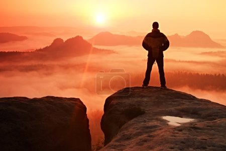 Man on peak of sandstone rock in national park Saxony Switzerland watching to Sun. Beautiful moment