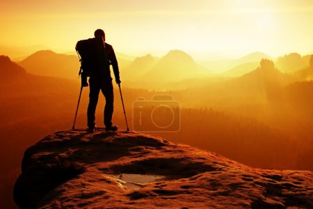 Photo for Tourist with medicine crutch above head achieved mountain peak. Hiker with broken leg in immobilizer. Deep misty valley bellow silhouette of man with hand in air. Spring daybreak - Royalty Free Image