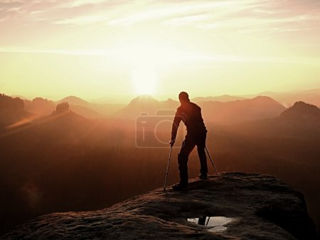 Photo for Bended man with broken leg and medicine crutch.  Hiker with leg in immobilizer achieve peak of mountain. Deep misty valley bellow silhouette.  Spring daybreak - Royalty Free Image