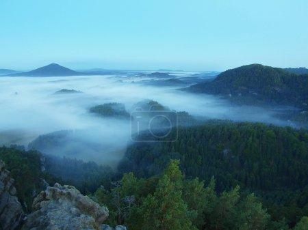 Photo pour Colline rocheuse au-dessus de la forêt de la mort et vallée embrumée. le brouillard se déplace entre les collines et les sommets des arbres, ciel bleu. - image libre de droit