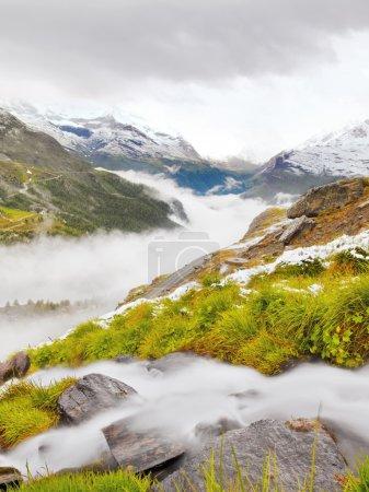 Photo pour Première neige sur la prairie alpine. Rapide ruisseau tombe sur des pierres de pantoufle à profonde vallée brumeuse. Sommets enneigés des Alpes en arrière-plan . - image libre de droit