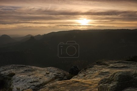 Photo for Sunrise in a beautiful mountain of Czech-Saxony Switzerland. Sandstone peaks increased from foggy background, the fog is orange due to sun rays. - Royalty Free Image