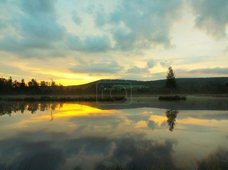 Photo pour Lac d'automne lever du jour avec niveau d'eau miroir dans une forêt mystérieuse, jeune arbre sur l'île au milieu. Couleur verte fraîche des herbes et de l'herbe, nuages roses bleus dans le ciel . - image libre de droit
