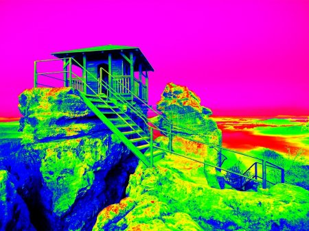 Infrared photo, wooden cabin on main peak of rock as view point, dark clouds in the sky. Summer early morning in sandstone rocks. Amazing thermography colors.