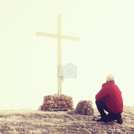 Tourist in red is kneeling at cross memorial on mountain peak. Misty Alpine winter day. Metal cross at a mountain peak.