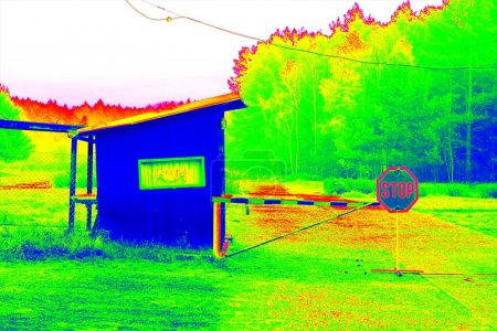 Gate and old gate house at small parking place at forest. Technical house and countryside in thermography scan.