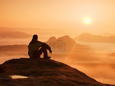 Photo for Hiker in black on the rocky peak. Wonderful daybreak in mountains, heavy orange mist in deep valley. Man sit on the rock and watch over the fog . - Royalty Free Image