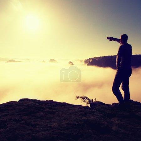 Photo pour L'homme en chemise et en jean est debout sur le sommet de l'empire de grès et veille sur la vallée brumeuse et brumeuse du matin jusqu'à Sun. Beau moment le miracle de la nature - image libre de droit