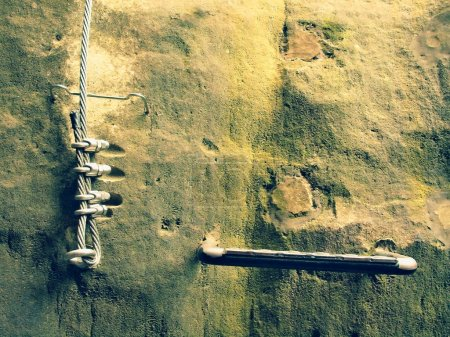 Climbers way. Iron twisted rope fixed in block by screws snap hooks. The rope end anchored into sandstone rock.