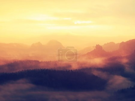 Photo pour Sunrise in a beautiful mountain of Czech-Saxony Switzerland. Hilly peaks increased from foggy background, the fog is orange due to sun rays. - image libre de droit