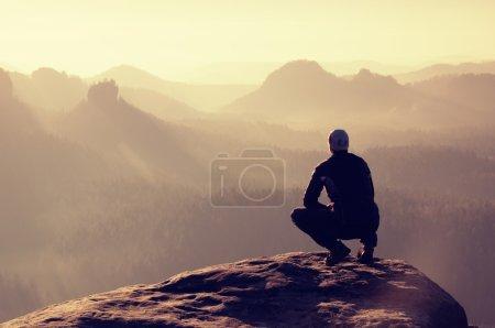 Photo pour Jeune homme en vêtements de sport noirs est assis sur le bord de la falaise et regardant au soufflet de vallée brumeux - image libre de droit