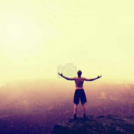 Gesture of triumph.. Climber in black pants. Naked tourist on the peak of sandstone rock in national park Saxony Switzerland watching into misty landscape.