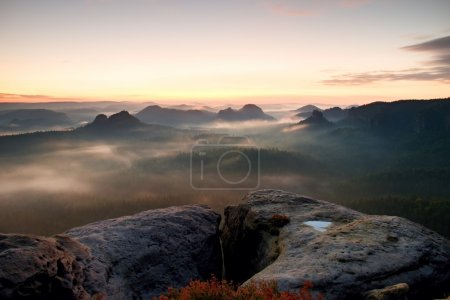 Kleiner Winterberg view. Fantastic dreamy sunrise on the top of the rocky mountain with the view into misty valley