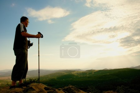 Tourist with camera on neck and poles in hands on peak of rock. Dreamy landscape bellow  in a beautiful valley below