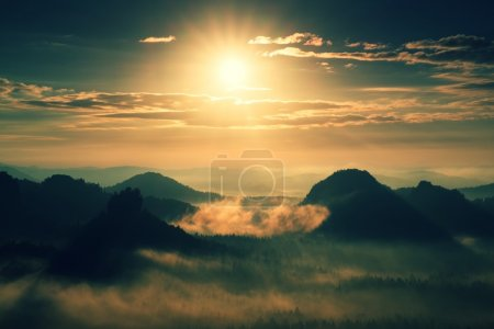 Heavy misty daybreak. Misty sunrise in  beautiful hilly park. Peaks of hills are sticking out from dense orange  fog.