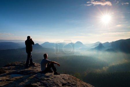 Photo pour Randonneurs et passionnés de photo restent avec trépied sur la falaise et la pensée. Paysage brouillard rêveur, lever de soleil bleu brumeux dans une belle vallée en contrebas - image libre de droit
