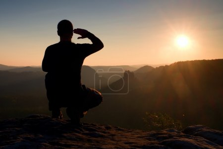 Photo for Tall hiker in squatting position  enjoy view at sunset on mountain peak - Royalty Free Image