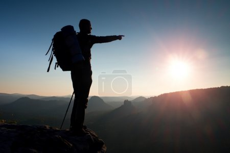 Sharp silhouette of a tall man on the top of the mountain with sun in the frame. Tourist guide in mountains
