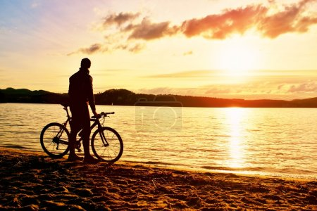Silhouette of sportsman  holding bicycle on lake bech, colorful  sunset cloudy sky in background and reflection in wavy water level