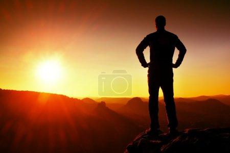 Photo pour Silhouette de jeune homme confiant et puissant, debout les mains sur les hanches, soleil de jour de retard avec espace copie - image libre de droit
