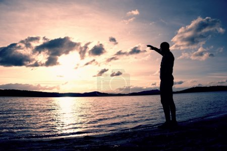 Man stand near beach looking at sunset, peaceful water level