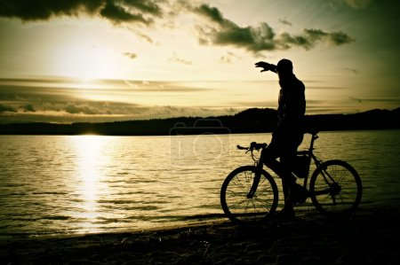 Silhouette of sportsman  holding bicycle on lake bech, colorful  sunset cloudy sky and reflection in wavy water level