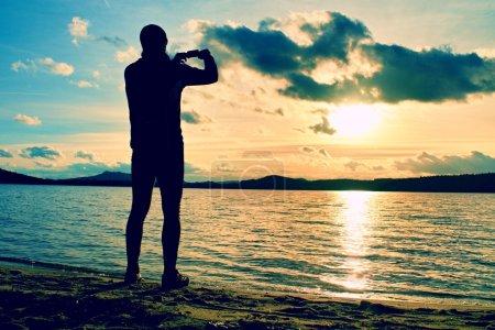 Foto de Turismo alto tomar fotos del atardecer con el teléfono móvil. Día de otoño en la costa del mar - Imagen libre de derechos