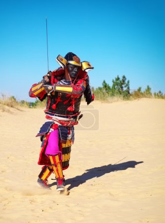 Man in samurai costume with sword running on the sand.