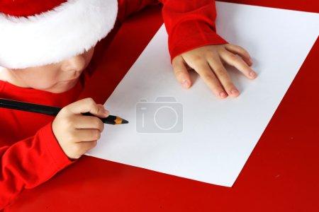 Foto de Niño de ayudante Navidad escribir carta a Santa Claus carta de sombrero rojo - Imagen libre de derechos