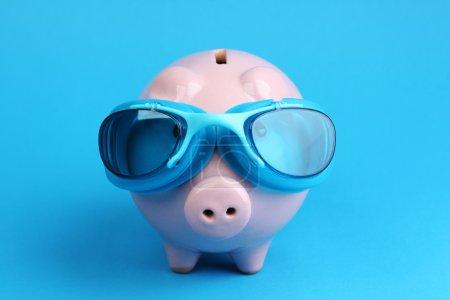 Photo pour Tirelire rose avec des lunettes de natation bleues sur fond bleu comme nageur - horizontale - image libre de droit