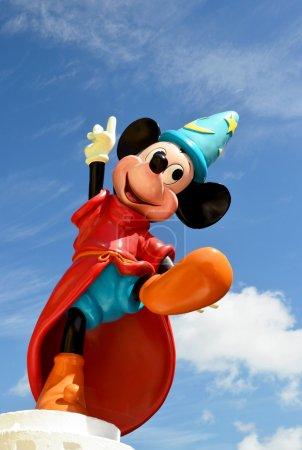 Foto de Monchique, faro - portugal, 30 de marzo de 2013. imagen del estudio de mickey mouse figura de pie sobre una pared con un fondo de cielo azul. Mickey mouse fue producido por walt disney - Imagen libre de derechos