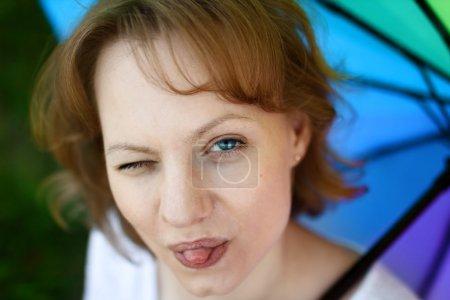 Photo pour Portrait de jeune fille drôle, qui est de s'amuser et d'affichage de langue, un œil est louchait, sur fond de parapluie multicolore. Concept de bonne humeur et de gaieté - image libre de droit