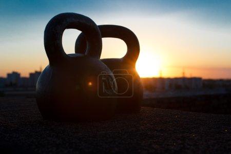 Photo pour Paire de noir one-pood kettlebells sur fond de coucher de soleil sur la ville. Concept d'accès pour l'amélioration de la santé et le développement physique en temps libre après une journée bien remplie - image libre de droit