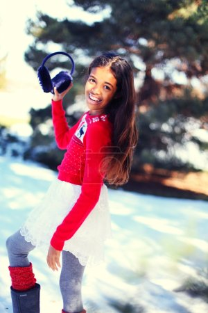 Photo pour Portrait d'une interpolation / jeune adolescente biraciale portant des cache-oreilles, pull de Noël et mitaines, dans le parc d'hiver - image libre de droit