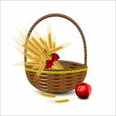 Sheaf of wheat ears in a wicker basket with red apples