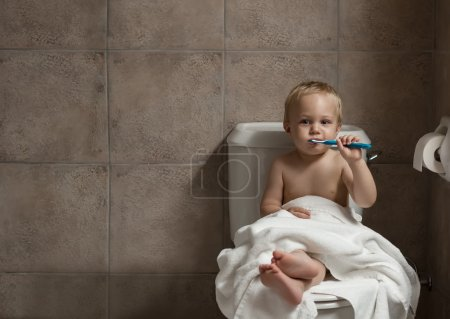 Toddler brushing his teeth after bath