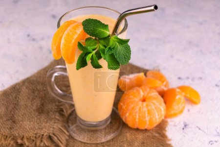 Photo for Tangerine smoothie with mint in a tall glass on a white plate. Close-up. - Royalty Free Image