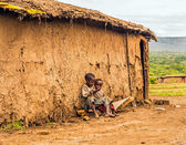 Two boys sitting in front of a Masai tribe village house