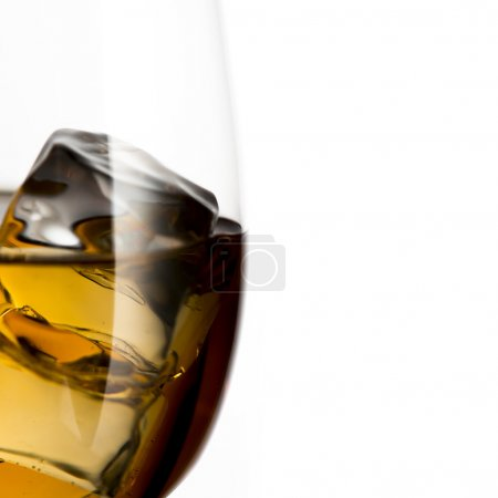 Whiskey in glass with ice cubes.