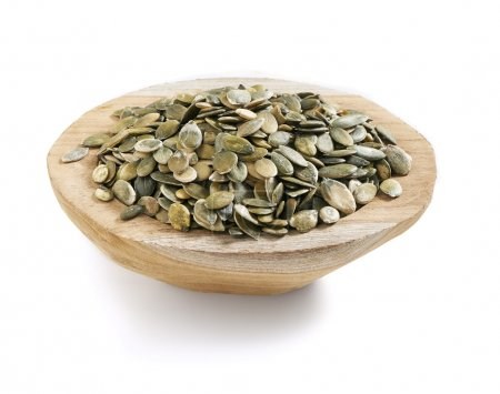 Photo for Healthy and tasty pumpkin seeds served in a wooden bowl with a soft shadow. - Royalty Free Image