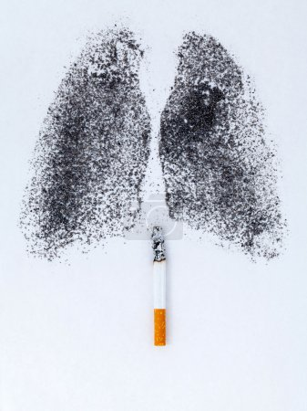 Shape of lungs with charcoal powder and cigarette on white backg