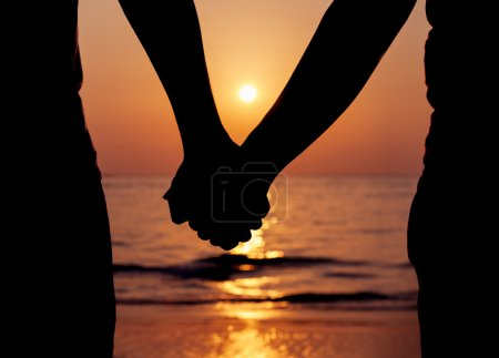 Photo for Silhouettes couples holding hands on sunset. - Royalty Free Image