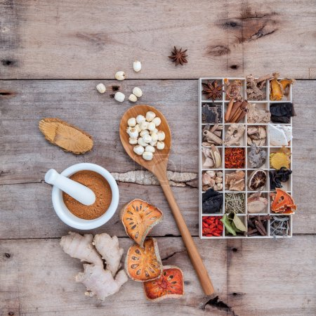 Photo for Alternative health care dried various Chinese herbs in wooden box and dried quince ,ginger and lotus seed in wooden spoon with mortar on old wooden background. - Royalty Free Image