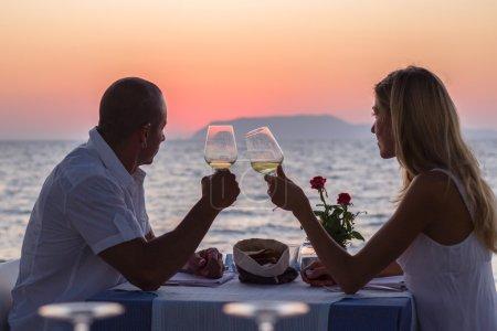 Photo pour Couple ont rendez-vous romantique au restaurant près de la mer au coucher du soleil - image libre de droit